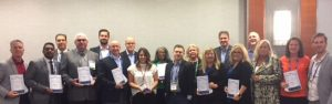 Shows a picture of many people receiving relocation awards, these awards were given to Paragon Relocation's top performing and top quality supplier partners by Paragon